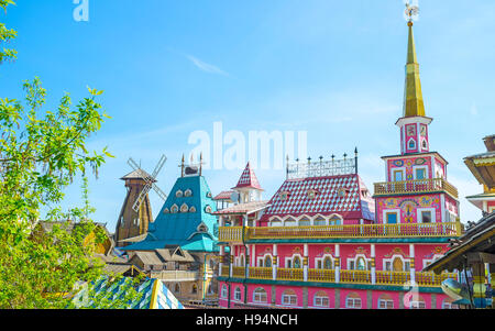 The colorful fairy tale mansion with golden spire, rooster weathervane and painted facade serves as hotel and craft - Stock Photo