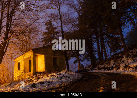 Beautifully lit village house in the forest against yellow streetlights.  Winter mountain scene - Stock Photo