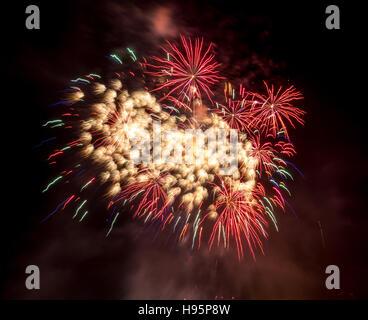 Fireworks bursting in the night sky on November the fifth, bonfire night - Stock Photo