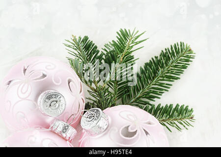 New pink Christmas baubles border with fresh pine over a white sparkly background. - Stock Photo