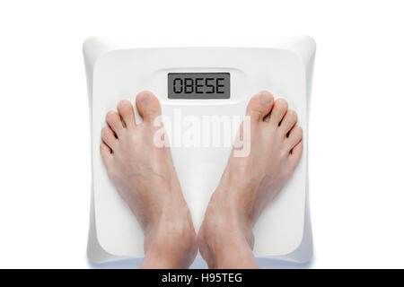 Feet on bathroom scale with the word OBESE on screen. Signifies either overweight health problems. - Stock Photo
