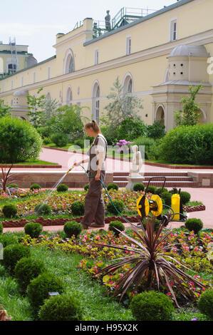 SAINT PETERSBURG, RUSSIA - JUNE 05, 205: a woman gardener watering flowers in the garden of Hermitage major art - Stock Photo