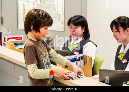 Japan, Nishinomiya, KidZania. Children's play world. Bank, interior, western child, 9-10 year old, withdrawing money - Stock Photo