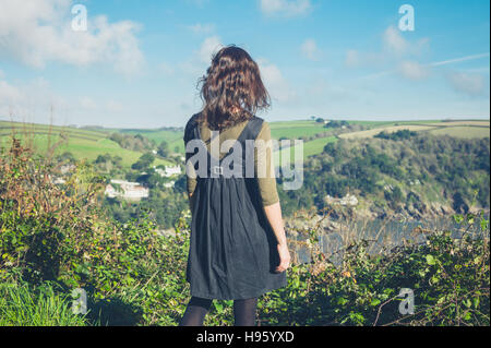 A young woman is standing on a hilltop and is admiring the countryside - Stock Photo