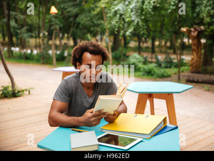 Serious african young man sitting and studying in the park - Stock Photo
