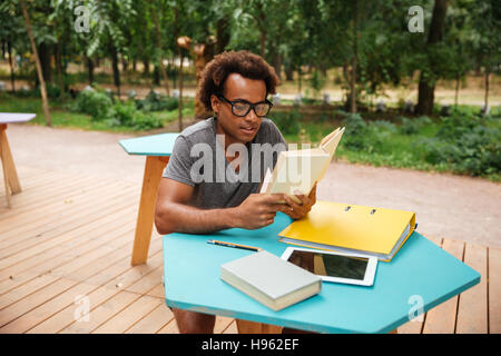 Concentrated african young man sitting and reading book outdoors - Stock Photo