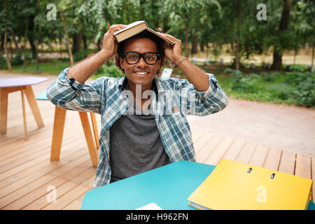 Happy african young man in glasses studying and having fun in outdoor cafe - Stock Photo