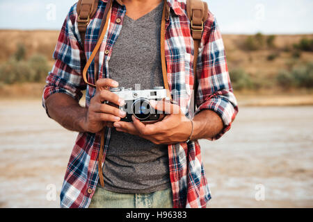 Closeup of man in plaid shirt standing and holding old vintage photo camera - Stock Photo
