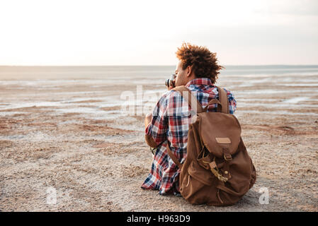 Back view of african young man with backpack sitting and taking photos on the beach - Stock Photo