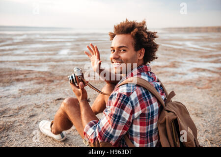 Cheerful african young man with backpack taking pictures with old vintage camera on the beach - Stock Photo