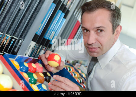 serious man prepares balls for start of game billiard - Stock Photo