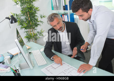 architects discussing on plans - Stock Photo