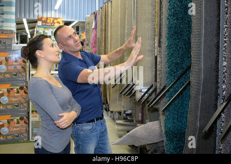 happy couple in store choosing wallpaper - Stock Photo