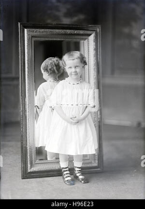 Antique c1900 photograph, toddler girl standing in front of a mirror. SOURCE: ORIGINAL PHOTOGRAPHIC NEGATIVE. - Stock Photo