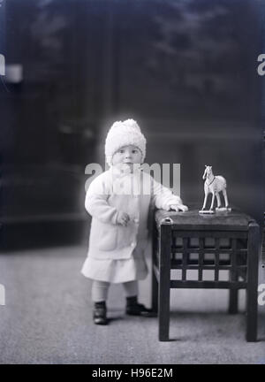 Antique c1900 photograph, toddler girl with horse toy. SOURCE: ORIGINAL PHOTOGRAPHIC NEGATIVE. - Stock Photo
