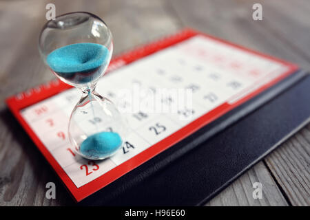 Hourglass on calendar - Stock Photo