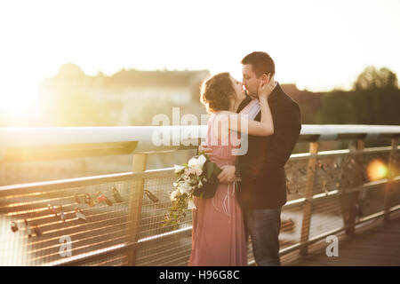 Stylish loving wedding couple, groom, bride with pink dress kissing and hugging on a bridge at sunset - Stock Photo
