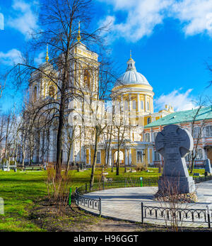 The memorial cross in garden of Alexander Nevsky Lavra and the Holy Trinity Cathedral behind the trees - Stock Photo