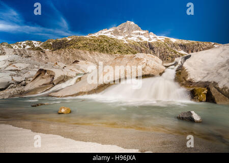 The start of Rhone river flowing from the small lake under Rhonegletscher - Stock Photo