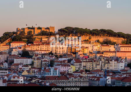 Cityscape of Lisbon, Portugal, with the Sao Jorge Castle seen from Miradouro Sao Pedro de Alcantara at sunset. - Stock Photo
