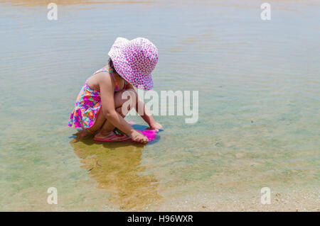 Little asian tourist girl playing in sea water puddle on the beach under summer sun. Always apply sunscreen before - Stock Photo