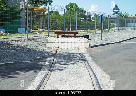 End of rail in an industrial area on against the background of a fence with barbed wire - Stock Photo