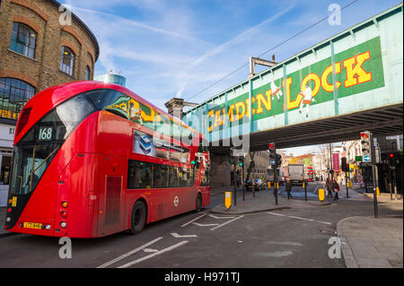 LONDON - NOVEMBER 16, 2016: A red double-decker bus passes under a railway overpass at the popular Camden Lock Market. - Stock Photo