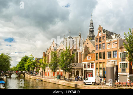 Amsterdam Red Light District canal with the Old Church (aka De Oude Kerk) among typical dutch houses, on a sunny - Stock Photo