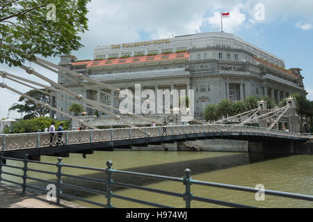 The Fullerton Hotel across Cavenagh Bridge, Empress Place, Civic District, Singapore Island, Singapore - Stock Photo