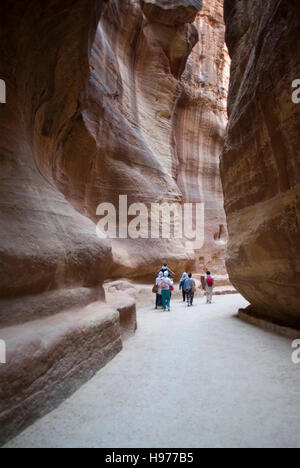 Tourists walking through the Siq, past ancient wall carvings, towards the entrance to Petra, Jordan - Stock Photo
