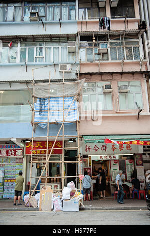 View of building in Hong Kong, with some bamboo scaffolding, stores on the lower level, and laundry hanging to dry - Stock Photo