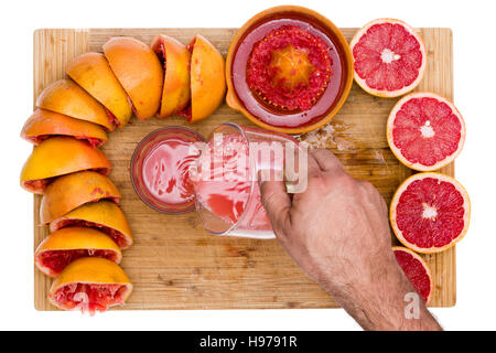 Man pouring freshly squeezed ruby grapefruit juice rich in soluble pectin fiber from a jug into a glass on a bamboo - Stock Photo