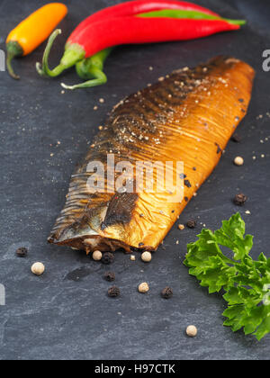 Smoked mackerel with pepper and cooking ingredients on a dark slate plate in a kitchen