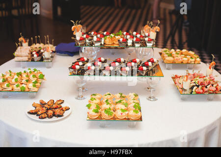 Table with assortment of canapes snacks. Banquet service. - Stock Photo