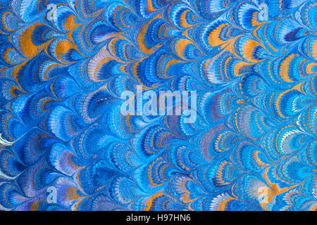 Hand marbled paper in peacock pattern. - Stock Photo