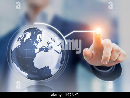 Worldwide business concept with 3D globe interface and businessman touching a button, global economy - Stock Photo