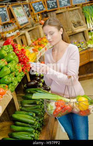 Young woman shopping at the greengrocer's - Stock Photo