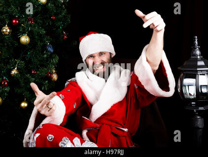 bad brutal Santa Claus smiles and showing middle finger sign on the background of Christmas tree - Stock Photo