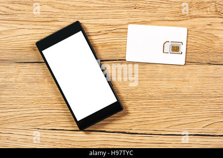 Smartphone With Blank Screen And Sim Card On The Table Top View