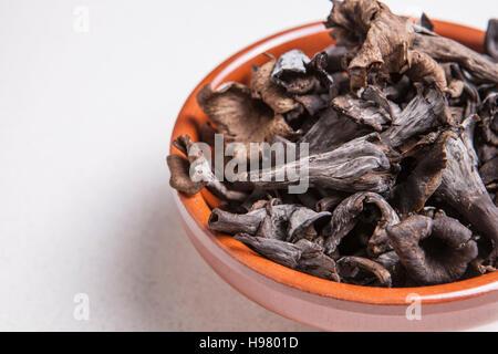 Clay bowl full of Horn of Plenty mushrooms. Isolated - Stock Photo