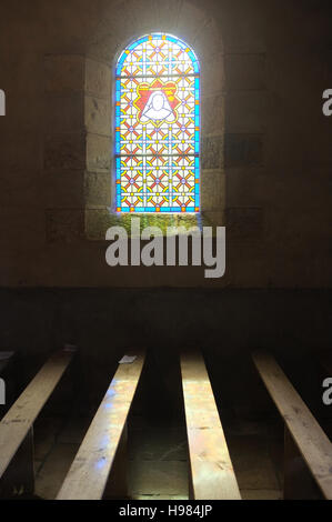 Church pews and stained glass window, Brittany - Stock Photo
