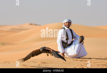 Dubai, UAE, November 19th, 2016: A falconer in traditional outfit, training a Harrier Hawk (Polyboroides typus) - Stock Photo