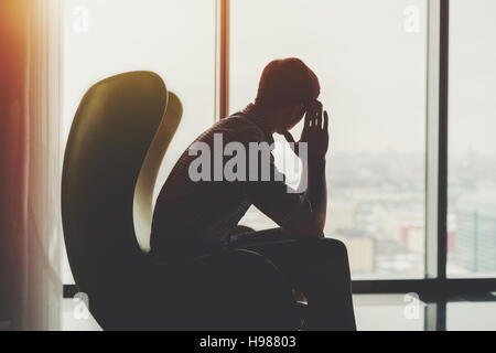 Silhouette of anxious and thoughtful businessman in checkered shirt sitting on yellow armchair and looking into - Stock Photo