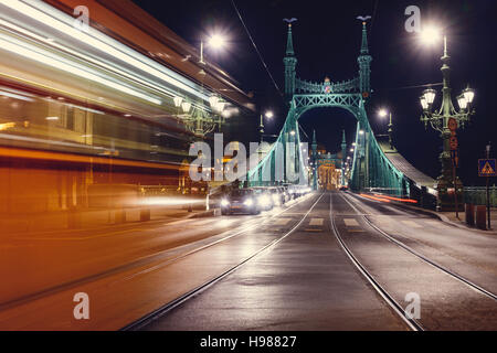 Night view at liberty bridge in Budapest with trams passing - Stock Photo
