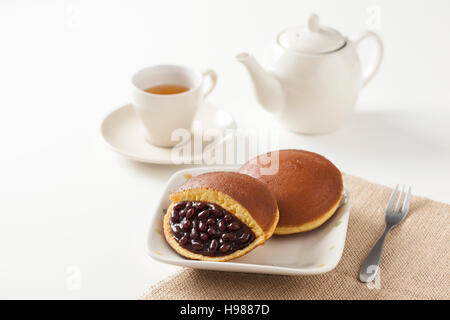 Traditional Japanese Red Bean Pancake, Dorayaki, with tea and teapot - Stock Photo