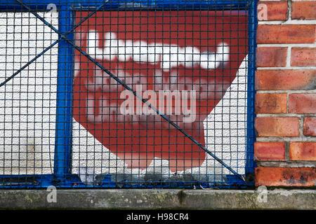 John Moores University sign seen through a broken window, Liverpool, Merseyside, UK. - Stock Photo