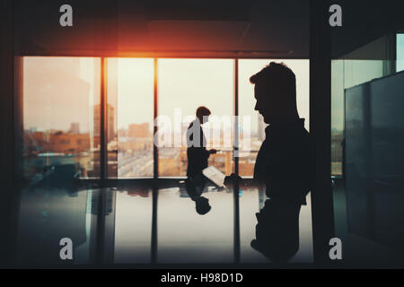 Silhouette of two businessmen working with their gadgets in office interior of skyscraper, man in front with digital - Stock Photo