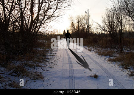 walking ahead silhouette of the man (3d character) on the snowy country road - Stock Photo