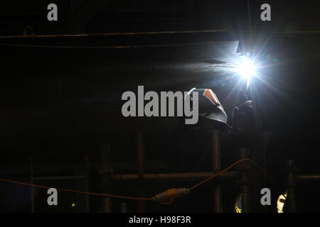 Welder at work in shipyard - Stock Photo