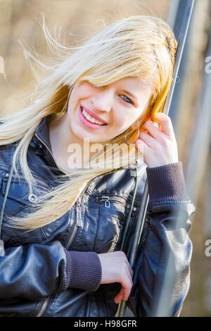 Beautiful teen girl blowing blow wind windy day flying blonde long blond hair holding hold hair attractive single - Stock Photo